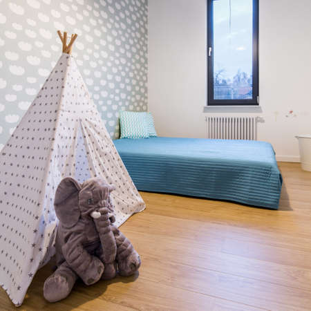 Cozy child room with bed, toy tipi tent and elephant mascot
