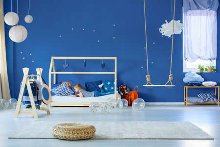 Young girl reading book in stylish scandinavian decorated bedroom
