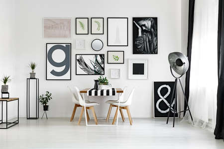 living room interior: Dining table by the white wall with posters in spacious lounge