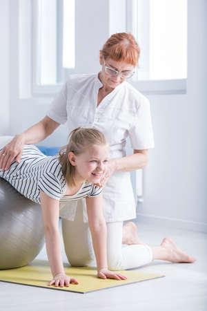 Fisioterapeuta femenina que apoya a niña con condición médica de la escoliosis
