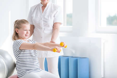 Physiotherapist and child exercising with yellow dumbbells in rehabilitation room