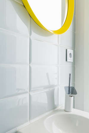 Rectangular white tiles in a modern bathroom, with a mirror in a yellow frame and a ceramic sink