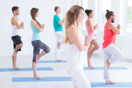 Focused young people standing on one leg in yoga club Imagens