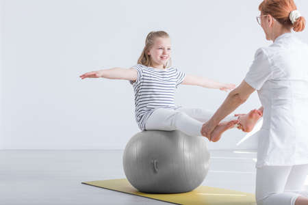 Smiling girl sitting on big gym ball working with physiotherapist