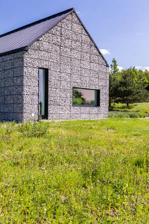 Modern house in the meadow, with pebble stone walls and narrow windows
