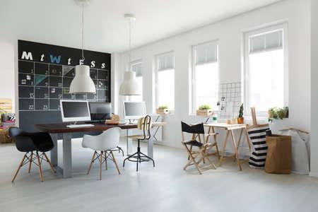 白の壁に黒板カレンダーとオープン スペースのトレンディなオフィス