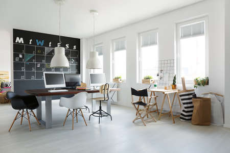 White open space trendy office with blackboard calendar on wall Imagens
