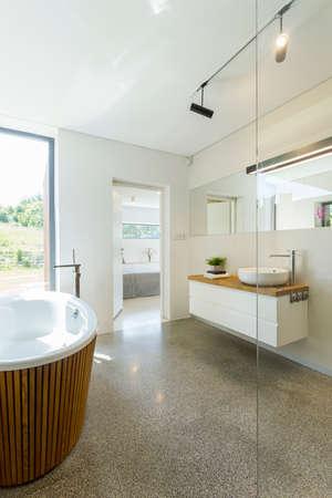 Luminoso bagno dal design semplice, con pavimento in granito, ampia finestra e vasca da bagno ovale Archivio Fotografico - 82517700
