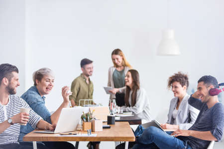 Caucasian coworkers having a good time chatting with their arabic colleague, during their break Stock Photo