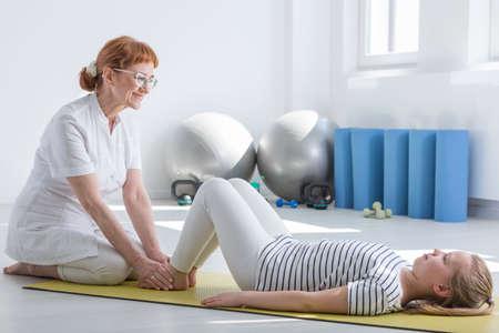 Fisioterapeuta de sexo femenino que trabaja con el niño en la habitación ocupacional brillante