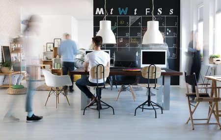 People walking in inspiring modern office with blackboard calendar