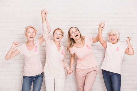 Group of smiling ladies with pink ribbons cheering and holding hands Standard-Bild