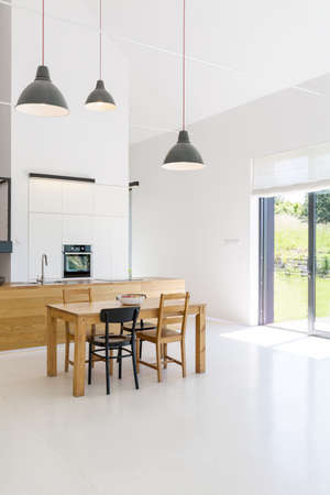 Spacious interior of a kitchen and dining room in a contemporary house, with white walls, floor and ceiling