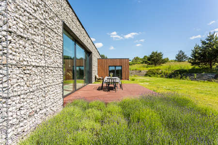 Modern pebble wall house with a deck terrace surrounded by wild flowers and grass Stock fotó