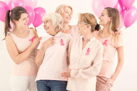 Glimlachende zelfverzekerde vrouwen dragen roze staand en tonen ondersteuning aan elkaar