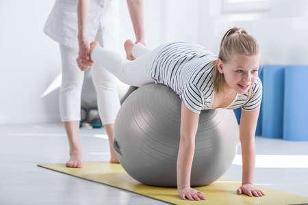 小児の作業療法中にボールの上に横たわる少女の笑みを浮かべてください。 写真素材