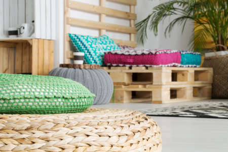 Simple pallet sofa in white room with trendy colorful decorations