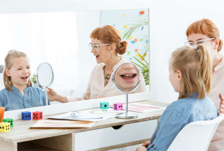 Speech therapist using fun mirror exercises during session with child