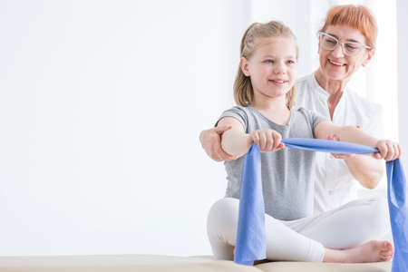 Female physiotherapist supervising little girl during stretching the rubber tape