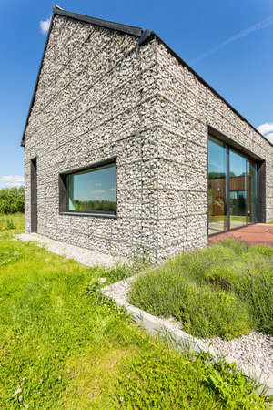 Modern pebble stone wall house with large windows, surrounded by wild grass