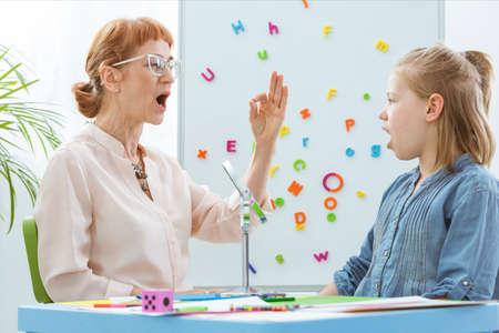 特殊教育の教師が少女のスピーチ療法時の操作