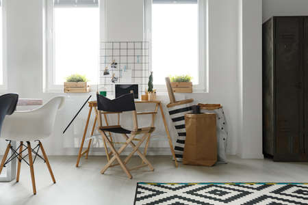 Simple wooden desk with folding chair in scandinavian white office Stock Photo