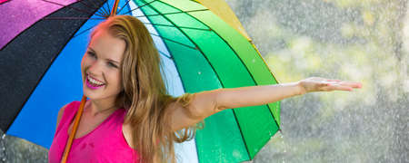 Woman under colorful umbrella checking if it is still raining