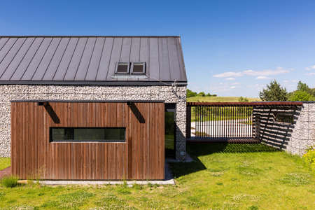 garage on house: Innovative house in the country, with pebble walls, wooden garage and metal fence