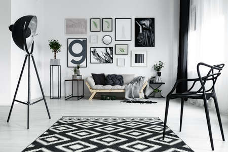 Black stylish chair in modern designed living room with posters