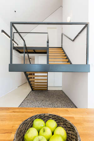 Massive staircase of modern shape, with decorative pebbles underneath, in a bright modern interior