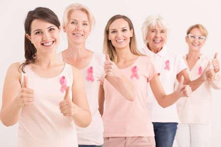 ピンクを与えて身に着けて幸せなエネルギッシュな女性のグループが親指します。