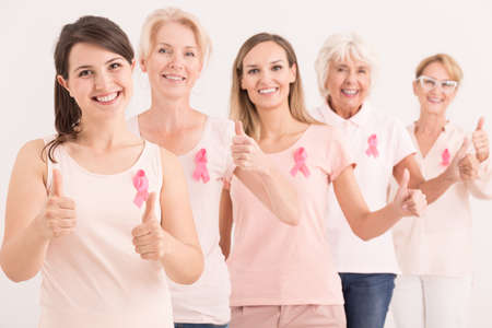Group of happy energetic women wearing pink giving thumbs up Stock Photo