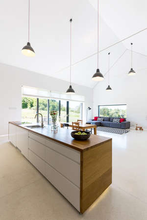 Open space of a modern houses interior seen from the perspective of a kitchen island Banco de Imagens