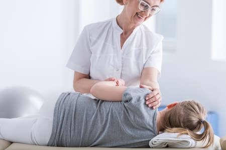 Female physiotherapist giving back massage to child on massage bed Stock Photo