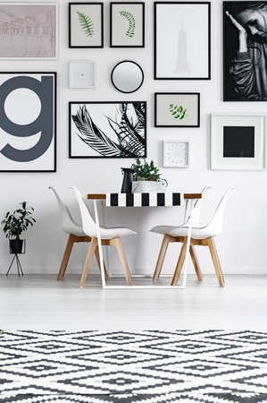 Dining room in black and white patterns with posters on the wall Stock Photo