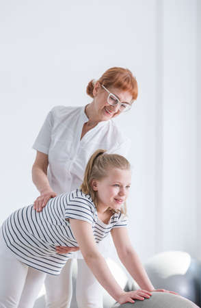 Child with spine deformity exercising with therapist in rehabilitation room