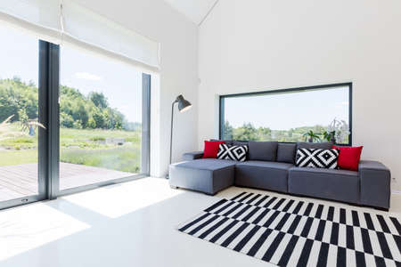 Very bright living room in a modern house, with a large corner sofa and panoramic windows overlooking picturesque neighbourhood Stock fotó