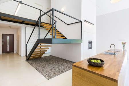 Modernistisch interieur met massieve trap van zwart metaal en hout, en ruimte vol met kiezelstenen onder Stockfoto - 82517941