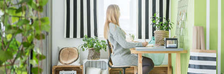 living room interior: Young woman at work in her stylish home office