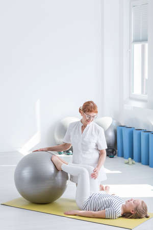 Little girl exercising on gym ball with professional child physiotherapist Stock Photo