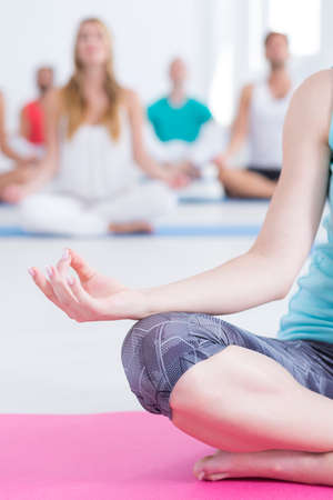 Close-up of woman meditating while doing yoga on mat