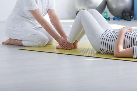 거품 매트에 잘못된 자세로 환자와 함께 운동하는 물리 치료사