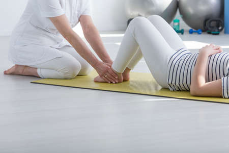 Physiotherapist exercising with patient with faulty posture on foam mat
