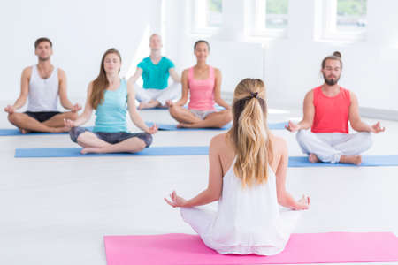 Exercise class meditating in lotus position while practicing yoga indoors