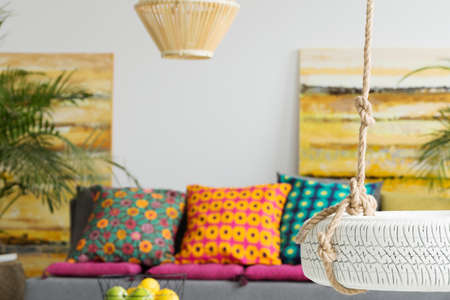 living room interior: Colorful decorative pillows in contemporary room with tire swing Stock Photo