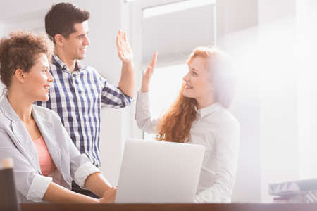 Successful business colleagues giving high five at desk in office Stockfoto