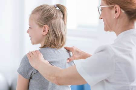 Child being given back massage for pain relief by chiropractor