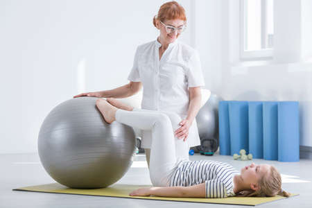 Child orthopedist using gym ball during rehabilitation with young patient