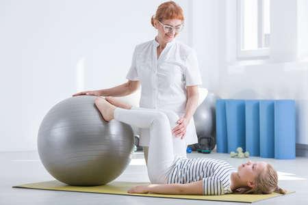 Niño, ortopedista, usando, gimnasio, pelota, durante, rehabilitación, joven, paciente