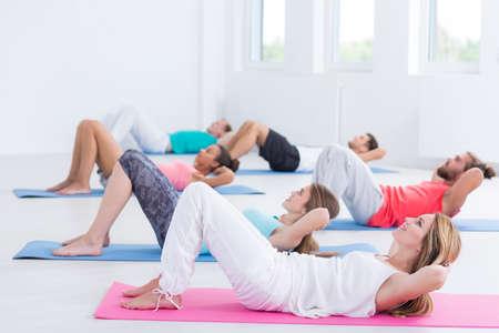Groep van diverse mensen die sit-ups doen in de fitnessoefening